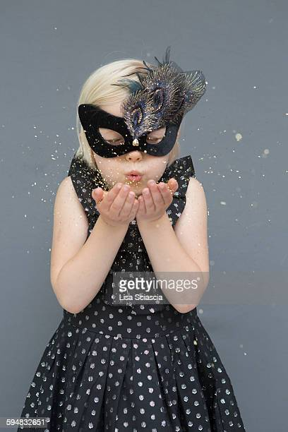 Girl wearing masquerade mask blowing glitters against gray background