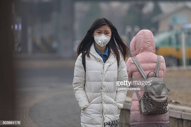 Girl wearing mouth mask with filter against air pollution, Beijing