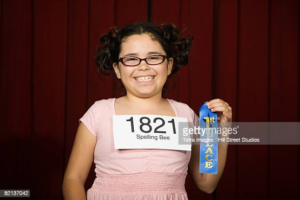 Girl wearing number and holding first place ribbon