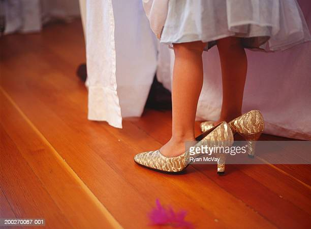 Girl (4-5) wearing oversize high heels, Close-up of feet