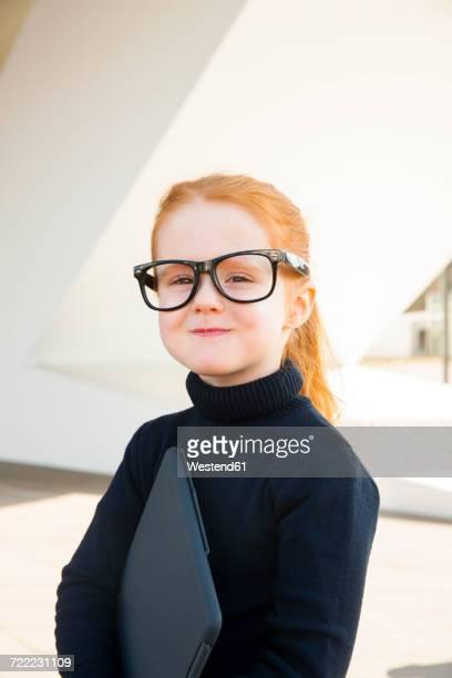 Girl wearing oversized glasses holding laptop