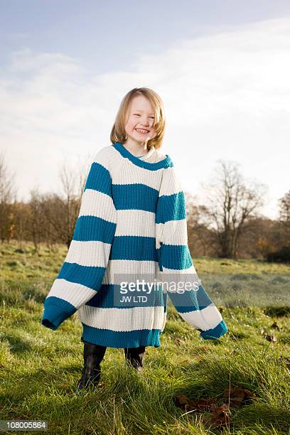 girl wearing oversized jumper, smiling - jumper stock pictures, royalty-free photos & images