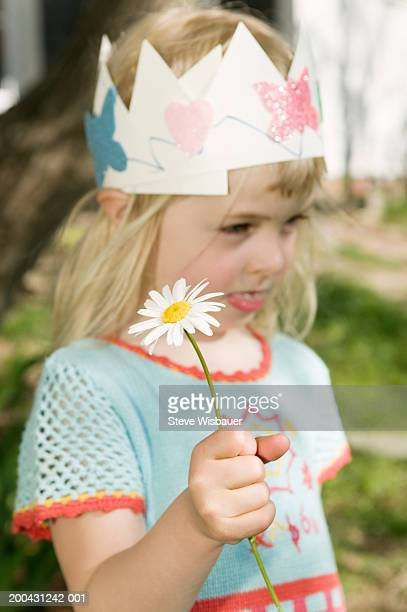 Girl (3-5) wearing paper crown, holding daisy