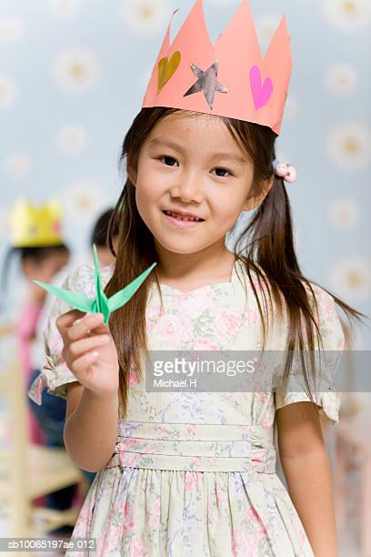 Girl (4-5) wearing paper crown, holding origami piece, portrait