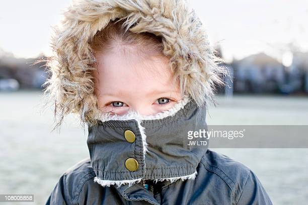 Girl wearing parka with mouth covered, portrait