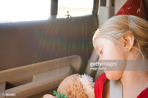 Girl wearing party hat asleep in car