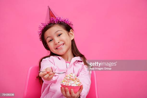 Girl wearing party hat, holding bowl of cake towards camera