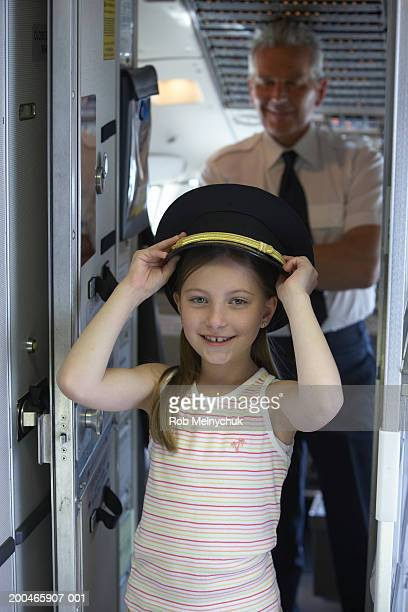 girl (6-8) wearing pilot's hat, pilot smiling in cockpit in background - aviation hat stock photos and pictures