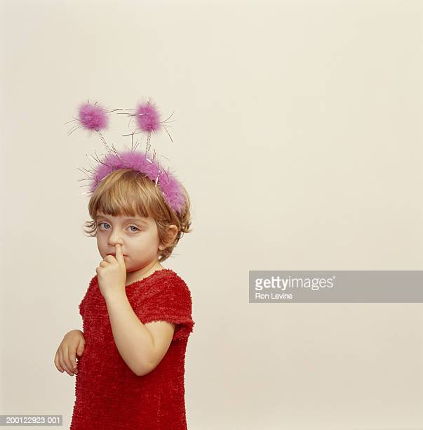 Girl (4-6) wearing pink antennae with finger in nose