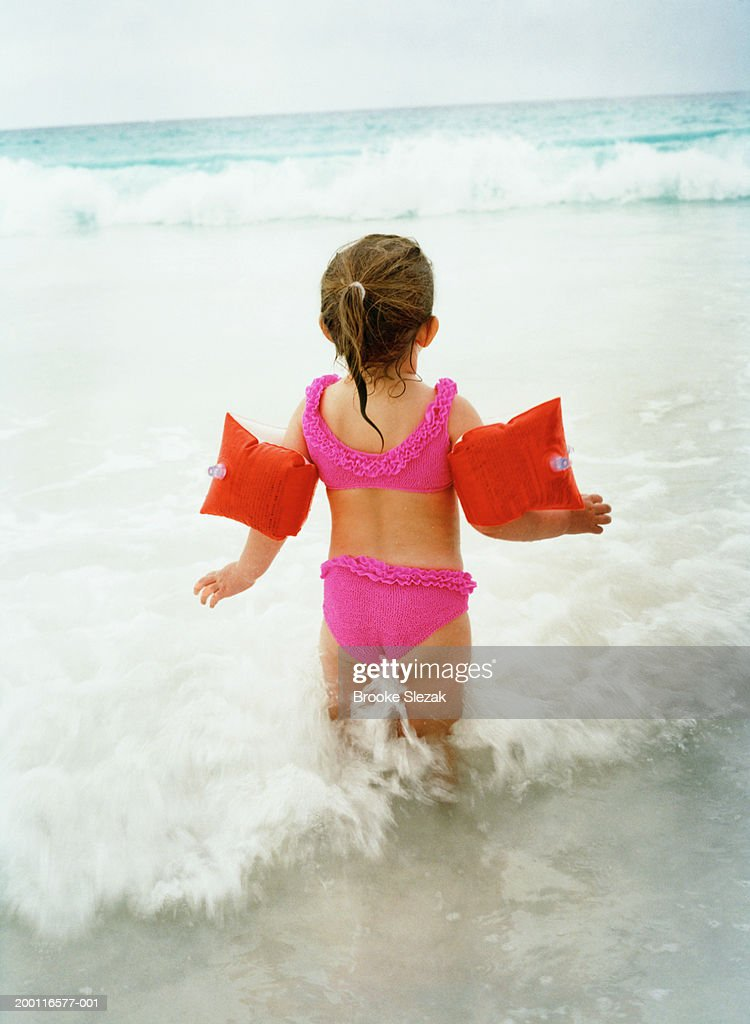 Girl (2-4) wearing pink bikini, standing in water at beach, rear view : ストックフォト