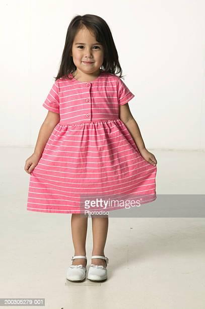 Girl (4-5) wearing pink dress posing in studio, portrait