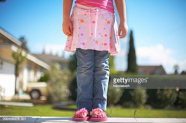 girl (6-8) wearing pink skirt and jeans, low section - girl wear jeans and flip flops stock photos and pictures