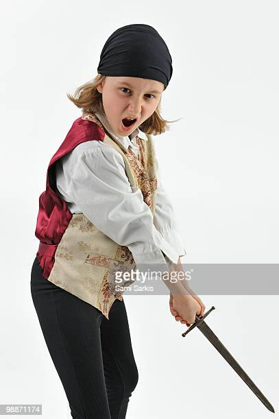 girl (9) wearing pirate costume, waving sword - female pirate stock photos and pictures