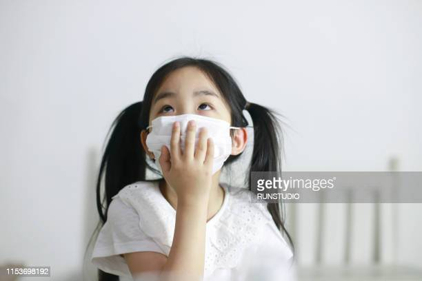 girl wearing protective face mask and cough - face mask protective workwear stock pictures, royalty-free photos & images