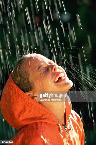 Girl (7-9) wearing raincoat, standing under shower of water