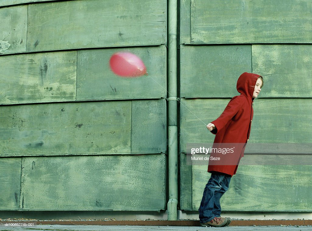 Girl (8-9) wearing red coat standing by green copper wall, holding balloon : Foto stock