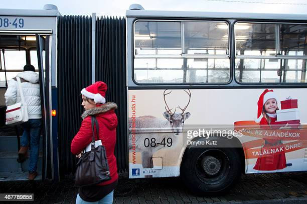 Girl wearing red jacket and red Santa Claus stocking cap with white trim boards a bus with another girl in Santa Claus' outfit and a rheindeer...