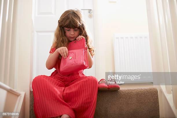 Girl wearing red on stairway looking in handbag