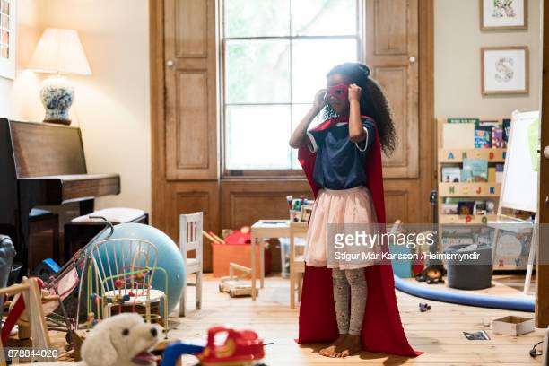 Girl wearing red superhero costume amidst toys