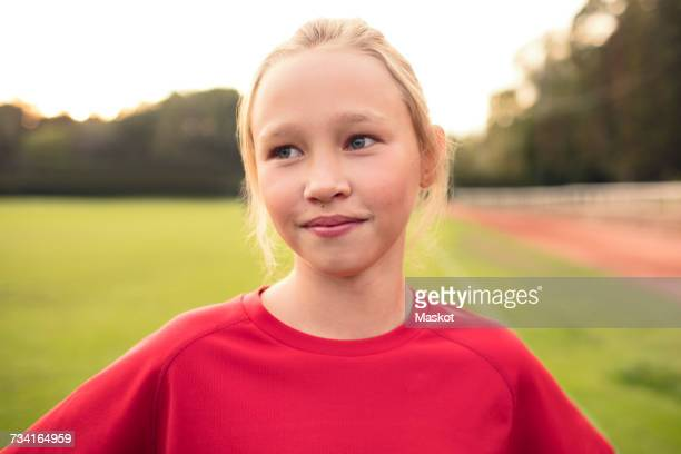 Girl wearing red t-shirt standing on soccer field against sky