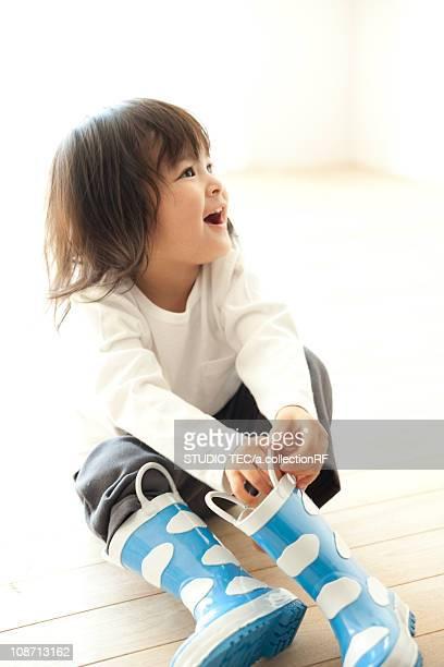 girl wearing rubber boots - レインブーツ ストックフォトと画像