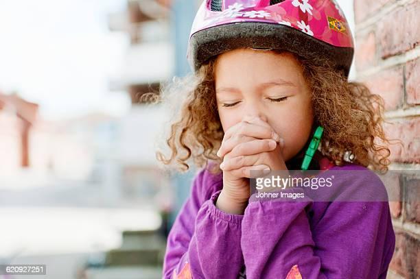 Girl wearing safety helmet, praying
