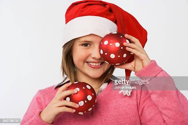 Girl wearing Santa hat holding Christmas bubbles