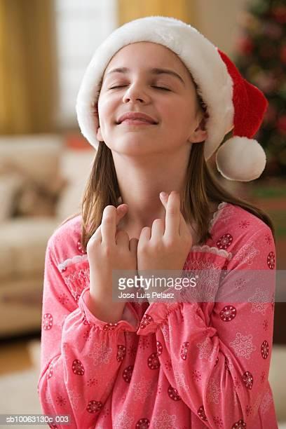 Girl (8-9 years) wearing santa hat standing in living room with crossed fingers