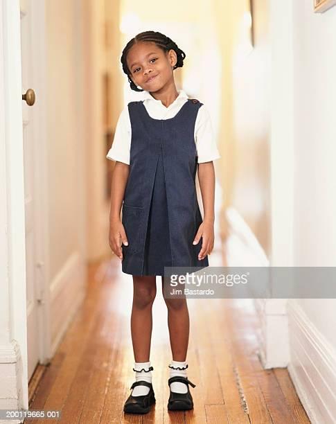Girl (6-8) wearing school uniform in hallway, portrait