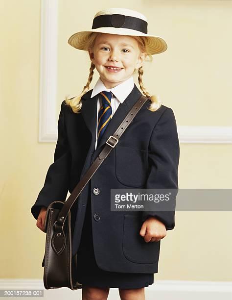 Girl (3-5) wearing school uniform, smiling, portrait