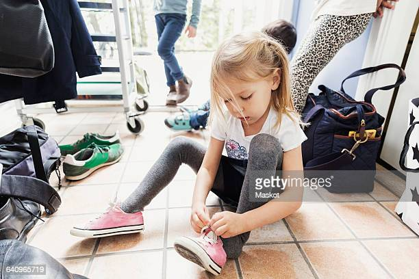 girl wearing shoe while sitting on floor at day care center - voorbereiding stockfoto's en -beelden