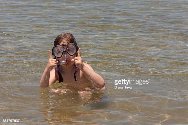 Girl wearing snorkeling mask in the sea showing size of fish with her hands