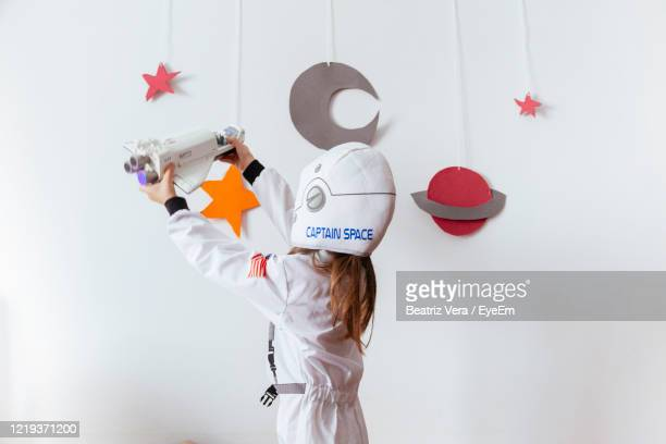 girl wearing space suit playing with rocket against wall at home - astronaut stock pictures, royalty-free photos & images