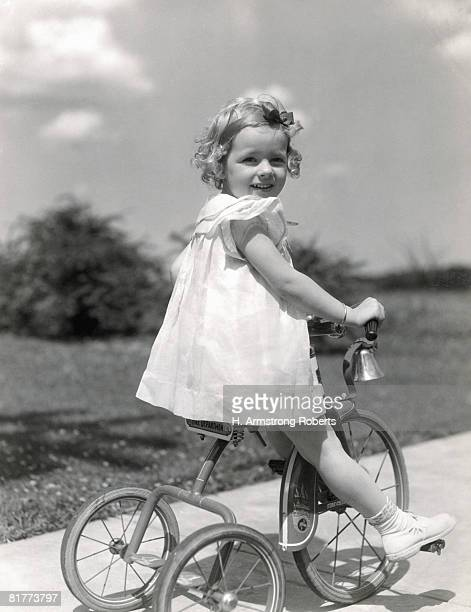 Girl wearing summer dress, riding tricycle down sidewalk. (Photo by H. Armstrong Roberts/Retrofile/Getty Images)
