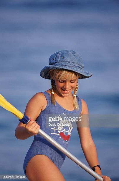 Girl wearing sun hat, standing holding paddles, looking down, smiling
