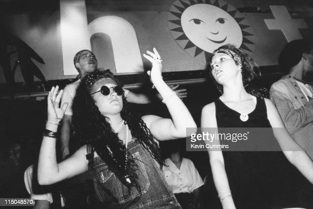 A girl wearing sunglasses and dungarees dancing in The Hacienda in Manchester at a popular acid house night 'Hot' July 1988