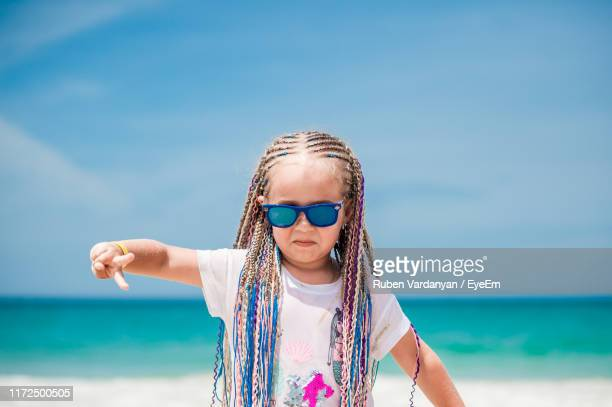 girl wearing sunglasses while gesturing at beach against sky - ruben vardanyan stock pictures, royalty-free photos & images