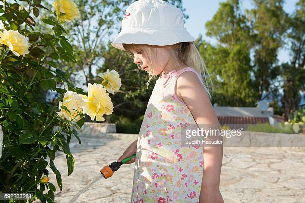 Girl wearing sunhat watering roses