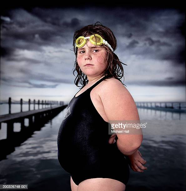 girl (7-9) wearing swimming costume by outdoor swimming pool, portrait - chubby stock photos and pictures