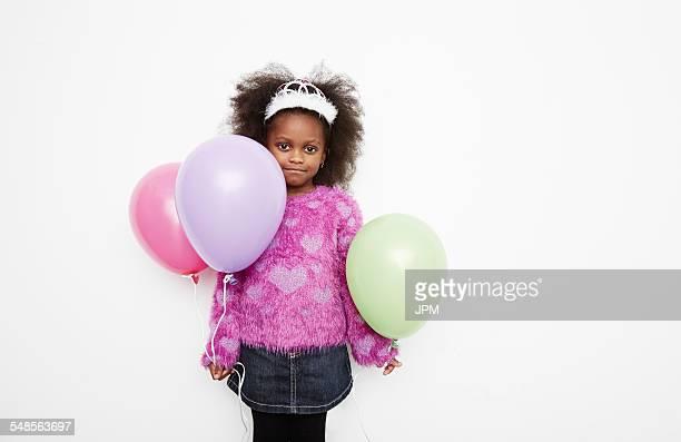 Girl wearing tiara and holding balloons