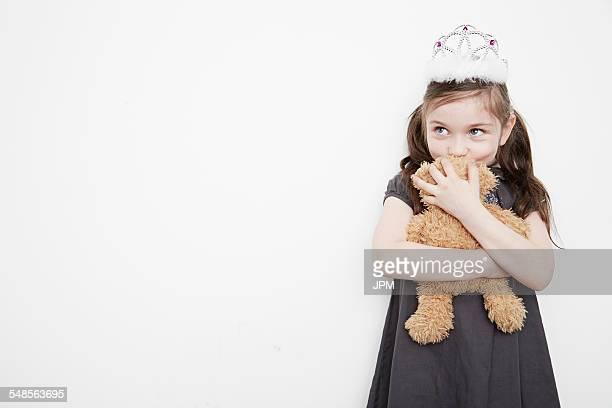 Girl wearing tiara holding teddy bear
