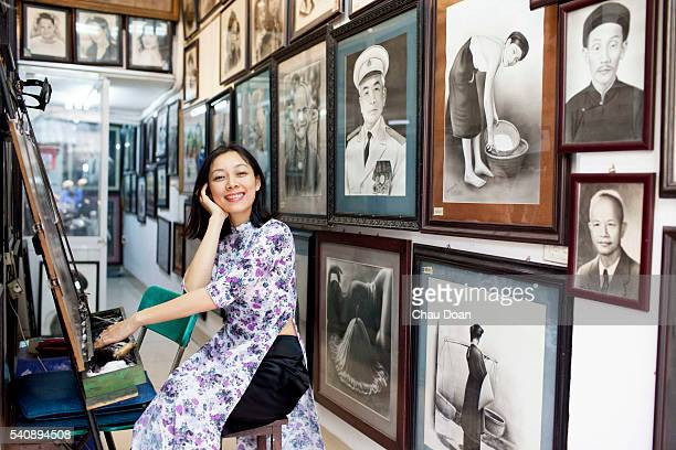 A girl wearing traditional dress called Ao Dai in a portrait copy shop on a street in Hanoi
