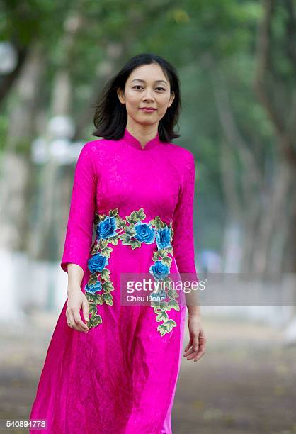 A girl wearing traditional dress called Ao Dai walks on the street of Hanoi
