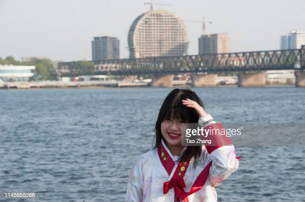 Girl wearing traditional Korean clothes pose for photos on April 28, 2019 in Dandong, China.The leader of the Democratic People's Republic of Korea ,...