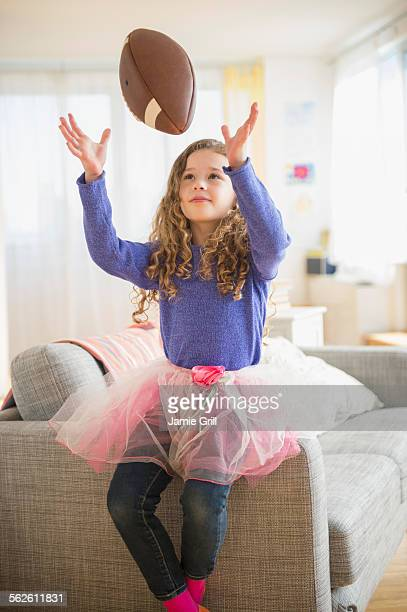 Girl (10-11) wearing tutu playing with football