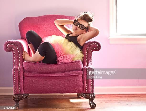 Girl wearing tutu posing on pink chair