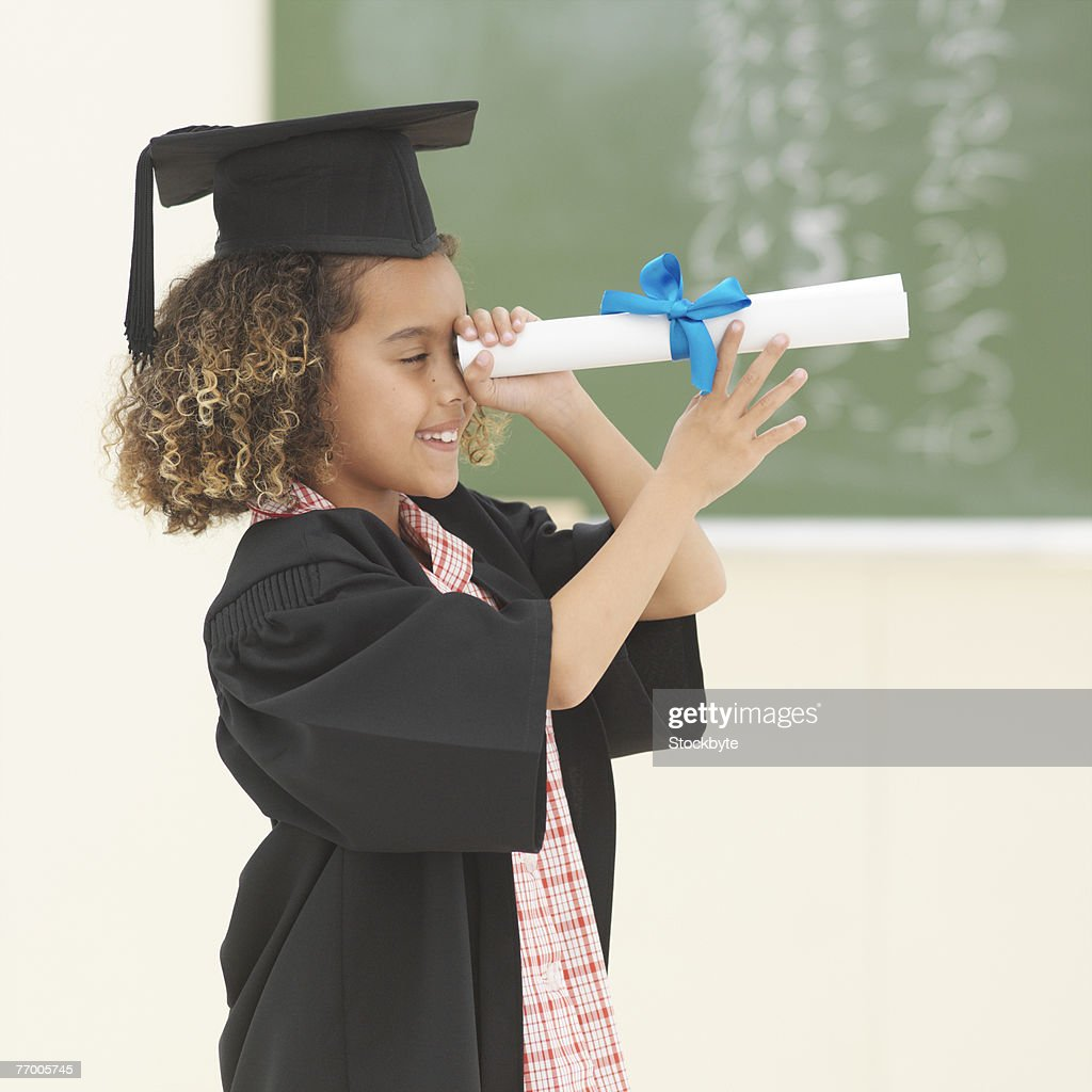 Girl Wearing University Gown And Mortar Board Looking Through Scroll ...