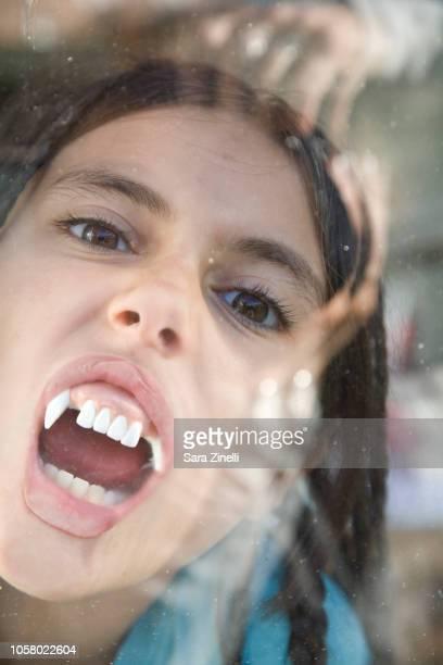girl wearing vampire teeth pressing her mouth against a window - buck teeth - fotografias e filmes do acervo