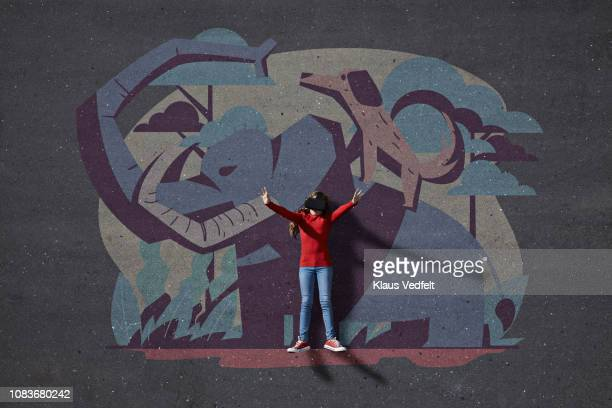 Girl wearing VR goggles in front of painted background of wild animals