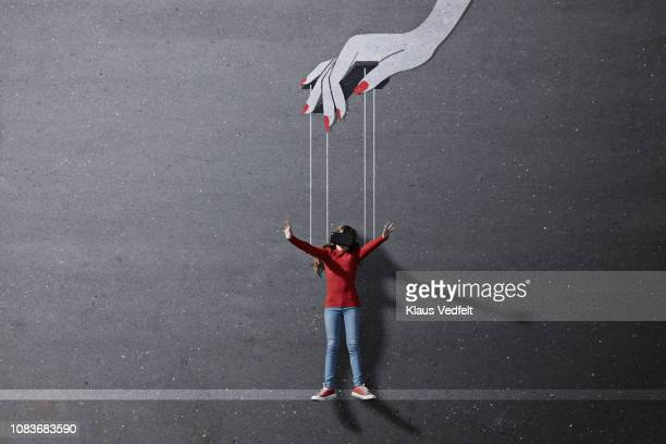Girl wearing VR goggles laying on background with imaginary painted puppeteer hand
